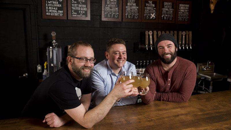 Слева направо: главный пивовар Брайaн Весткотт, профессор университета Виннипега Матт Гиббс, совладелец пивоварни Тайлер Берч.