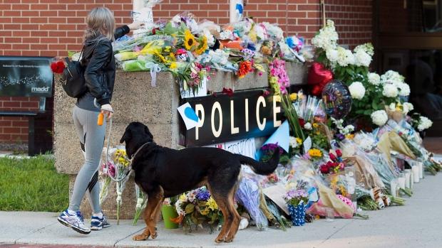 Люди несут цветы к отделению полиции Фредериктона, где работали погибшие